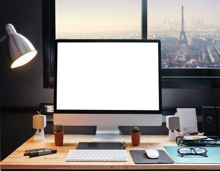 Graphic designer's workspace with cityscape view with a pen tablet, a computer and white background for text