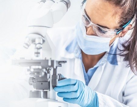 Female lab technician in protective glasses, gloves and face mask sits next to a microscope and conical flask, looking aside on the desk - panoramic banner.
